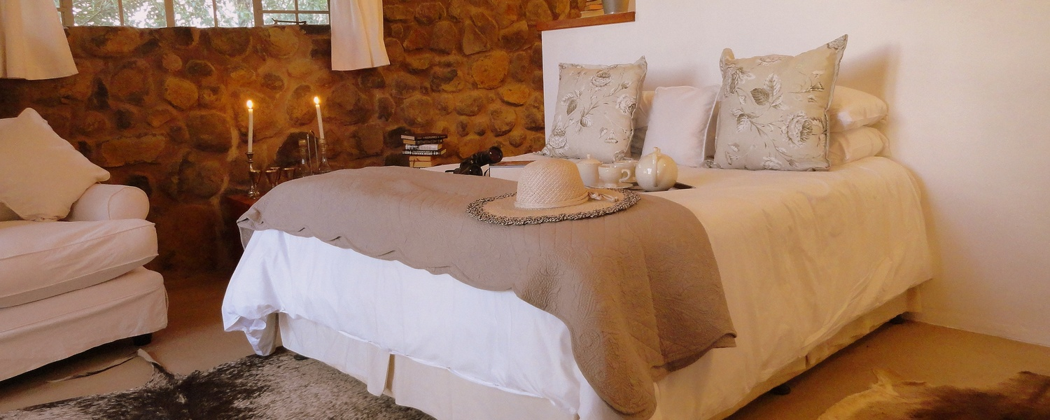 Porcupine Self Catering Cottage bedroom en suite with beautiful percale linen, heated blankets, leads out onto big veranda with a view.